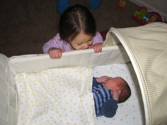 Kara looking at Nathan bassinet